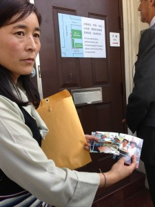 Lhamo Tso showing pictures of her children. Chinese Consulate in San Franciso (photo: Filming for Tibet)